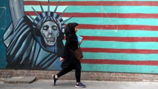 A woman passes a mural painted on the wall of the former US Embassy in Tehran, Iran, on 9 May 2018