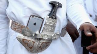 Điện thoại di động iPhone đuợc gài vào đai ngay cạnh con dao găm Omani truyền thống tại buổi lễ ở Muscat, Oman (5/11/2016)