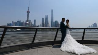 A couple posing for wedding photos with the Shanghai skyline in the background