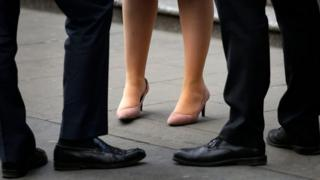 The legs of two men and a women in business attire