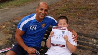 Dino Maamria with a child and a letter