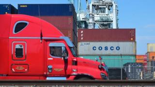 In this file photo taken on July 6, 2018 a container delivery truck passes containers stacked at the Port of Long Beach in Long Beach, California including one from COSCO, the Chinese state-owned shipping and logistics company.