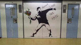 A mural on an interior prison wall - a copy of the Banksy picture of a youth throwing flowers