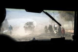 Iraqis walking in dust while a convoy of armoured vehicles passes them in eastern Mosul