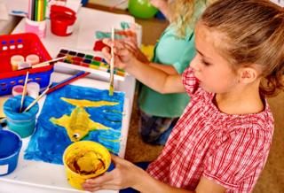 Child painting with yellow