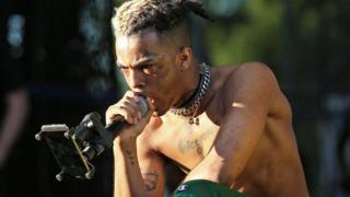 XXXTentacion performing on stage topless at outdoor event