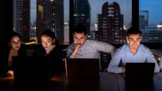 Hombres y mujeres trabajando en un turno noche.