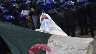 An Algerian woman holds a flag near security forces cordoning-off a protest area during an anti-system demonstration in Algiers, Algeria - Wednesday 10 April 2019