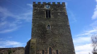 The clock stands at the top of the 12th Century St Mary's church