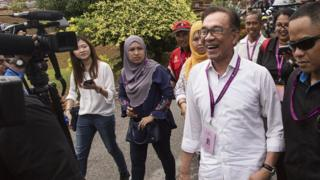 Anwar Ibrahim enjoys a light-hearted moment with member of the media at a polling station