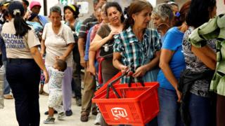 People line up to buy food and other staple goods inside a supermarket in Caracas, Venezuela on 30 June
