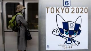 Technology A passenger wearing a face mask stands next to a poster of Tokyo 2020 Olympic mascot Miraitowa on a train in Tokyo on April 20, 2020