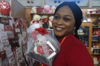 A woman smiles as she holds Valentine's Day gifts in a shop in Lagos' main airport on 13 February 2019. Supermarkets and shops stockpiled with Valentine's Day flowers and cards across the country are recording low sales because people are preoccupied with upcoming elections due on 16 February,