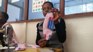 """Une employée de l'ONG Sacode montre à la correspondante de BBC Afrique une serviette """"agateka""""."""