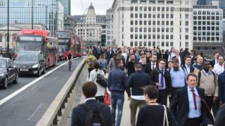 Commuters walk across London Bridge