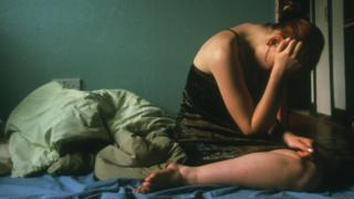 Distressed woman on bed - file pic