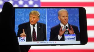 Donald Trump and Joe Biden at Cleveland presidential debate seen through a mobile phone screen