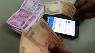 An Indian man checks the currency exchange rate on a mobile phone in New Delhi on November 24, 2016. India's rupee headed towards a record low against the dollar November 24, weakened by the government's shock currency shake-up and a greenback surge on expectations of a rate hike next month.