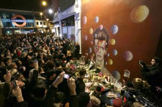 People gather at a mural of singer David Bowie by artist Jimmy C, in Brixton, south London.伦敦南部,民众在一幅由吉米·C创作的大卫·鲍伊壁画前致敬