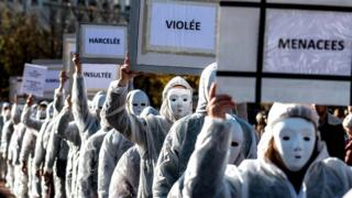 Protestors dressed in white carry placards as they take part in a demonstration in Lyon on November 24, 2018 marking the International Day for the Elimination of violence against Women