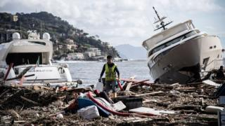 A man walks through garbage between two yachts after a storm hit the harbour and destroyed a part of the dam during the last night on October 30, 2018