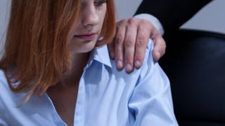 A generic image of a woman with a man's hand on her shoulder at work