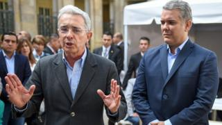 Mr Uribe gestures with open palms next to a younger Mr Duque, standing to attention nearby