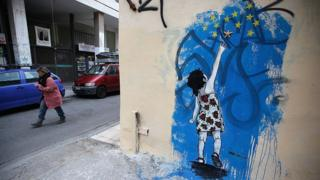 A woman walks past graffiti depicting a young girl trying to reach stars from the EU flag on 18 February 2012 in Athens, Greece