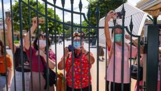 Hong Kong Disneyland visitors wearing protective face masks take photographs behind a fence.