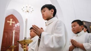 2018年12月24日,年轻的基督教徒在北京一所教堂参加弥撒。