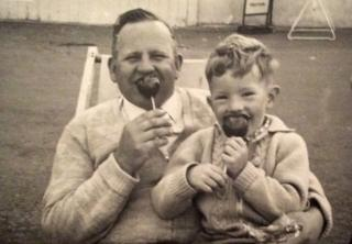 Ian eating a toffee apple with his dad