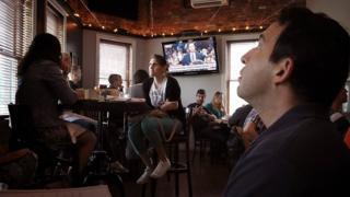 Посетители кафе перед телевизором