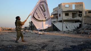 Turkish-backed rebel holds up flag in Al-Bab