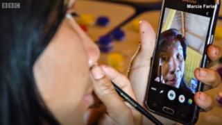 Mujer Kuikuru utilizando un celular para pintarse.