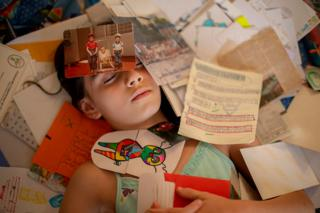 A girl lies on the floor covered with photos and papers