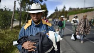 A Venezuelan man carries his baby as he walks along the Pan-American highway in Colombia on the way to Peru