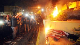 Protesters burn the US flag during a march in support of the caravan of migrants, in Tegucigalpa, Honduras