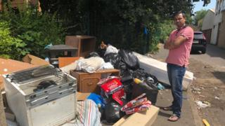 Cllr Enam Haque stood by a pile of rubbish on a street in Northampton.