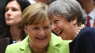 Theresa May (R) laughs as she talks with German Chancellor Angela Merkel at an EU leaders summit in Brussels, on June 22, 2017