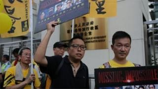 Protesters hold placards outside the Chinese Liaison Office in support of Lam Wing-kee, one of five Hong Kong booksellers who went missing last year, during a rally in Hong Kong (18 June 2016)