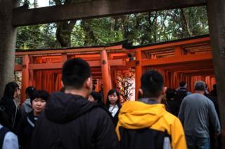 A crowd of tourists wait to access famous Torii path at Fushimi Inari taisha in Kyoto. 29 April 2019