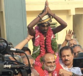 Mr Rangarajan is seen carrying Aditya on his shoulders as he enters the temple.