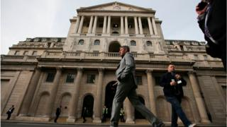 People walk past the Bank of England
