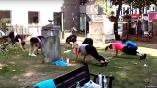 People exercising in graveyard