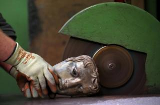 A foundry worker grinds and polishes a partially finished bronze mask.