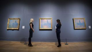 Members of staff look at paintings of the Houses of Parliament by Claude Monet during a photo call for EY Exhibition: Impressionists in London, French Artists in Exile (1870-1904) at the Tate Britain. 30 October 2017.