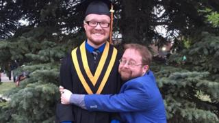 Allan hugs a taller man