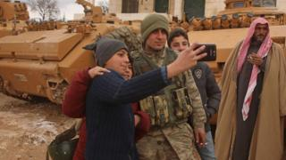 صبية سوريون يلتقطون صورا مع جندي تركي