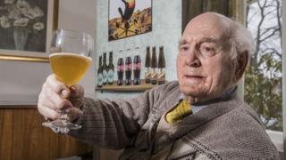Care home resident enjoying a beer
