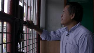Ali Fauzi looks through bars in a prison